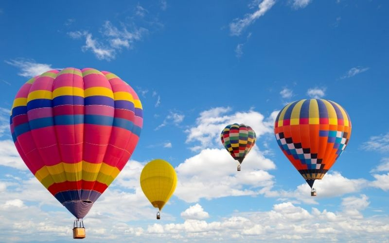Four hot air balloons floating in the sky.