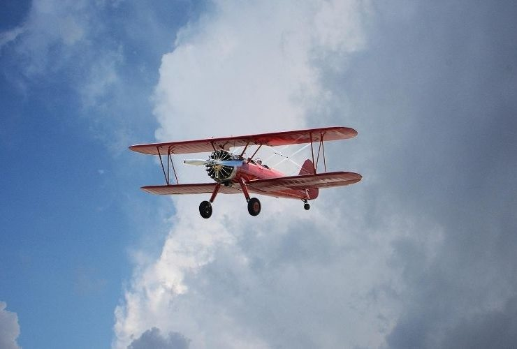 Red biplane flying in the sky.