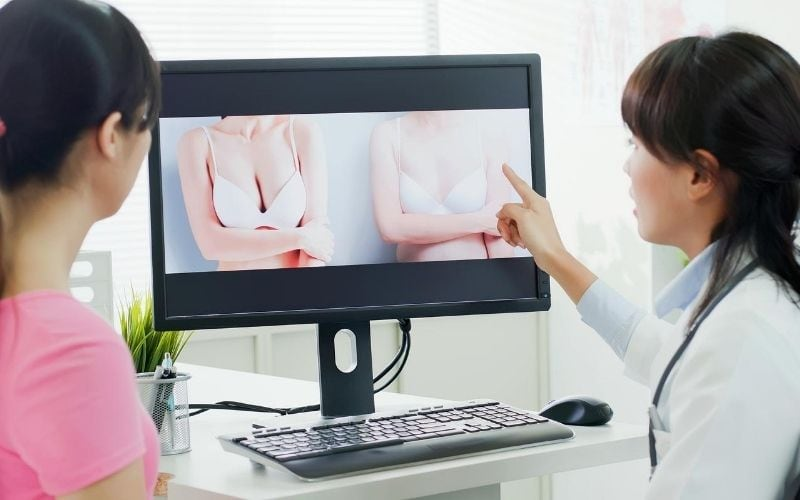 Woman sitting with her doctor looking at a preview of her breast reduction surgery on screen.