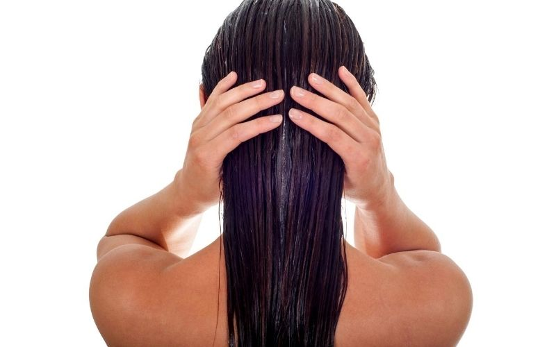 Woman washing her hair (back view).