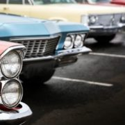 Photo of classic cars lined up in parking spots.