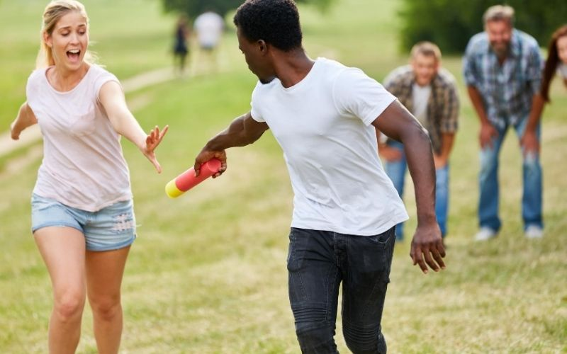 Teenagers doing a relay race on a green field.