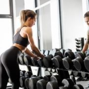 Woman grabbing weights at the gym.