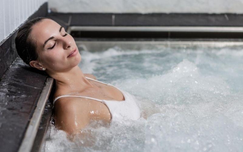 Woman relaxing in spa bath.