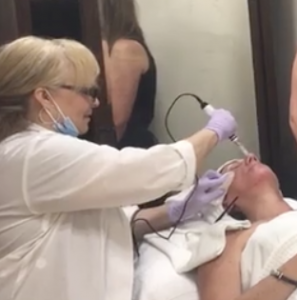Anne performs microneedling on Patti's face.