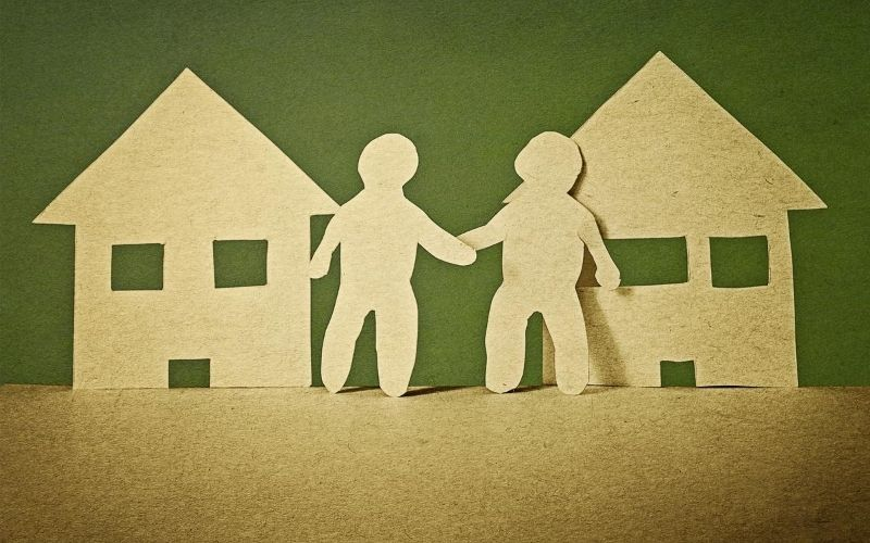Two cut out figures holding hands with houses behind them.