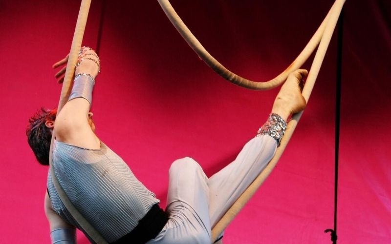 Acrobat hanging from ropes.