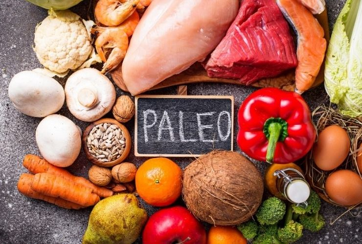 """Fruits, vegetables and grains surrounding chalkboard that says """"Paleo""""."""