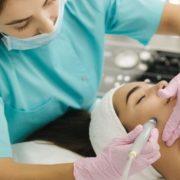 Esthetician preforming a hydra facial on a client.