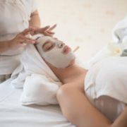 Woman receiving face mask at spa.