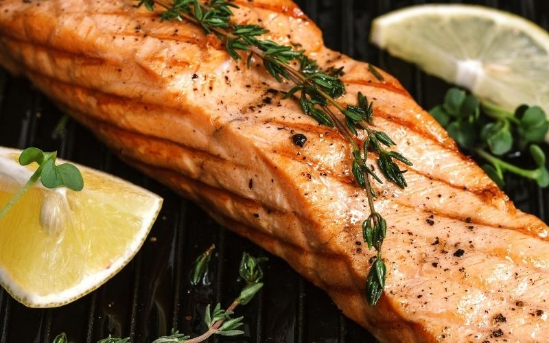 Grilled salmon with lemon wedges.