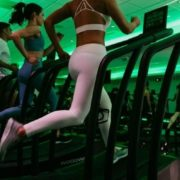 Women running on treadmills with neon green lighting in gym.