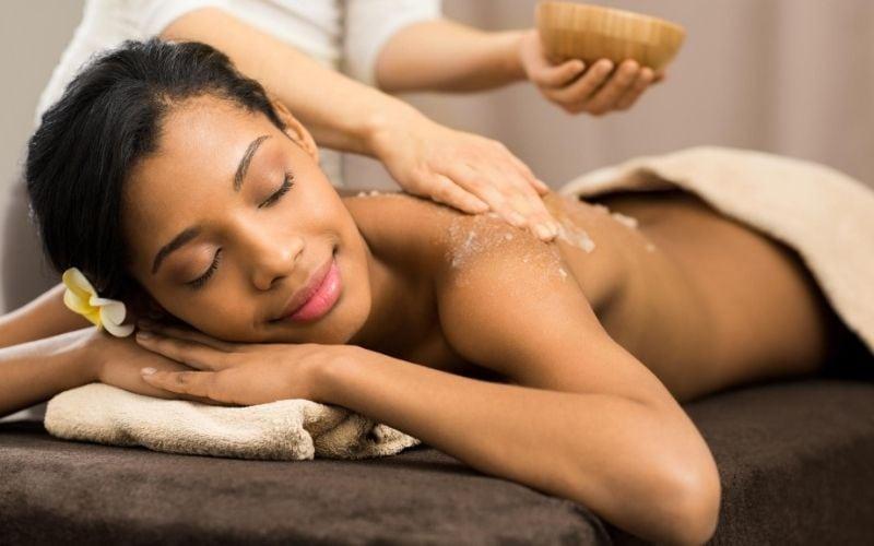 Woman getting a salt scrub at spa.