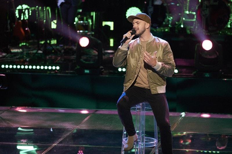 Musician, Alex Guthrie, singing on stage.