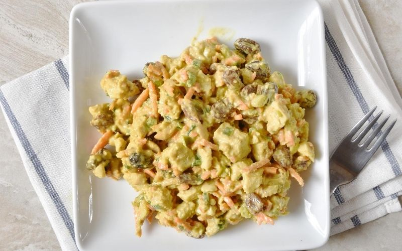 Curry chicken salad on a square, white plate.