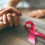 People holding hands with pink breast cancer ribbon on table.