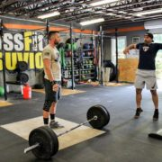 Crossfit instructor demonstrating a lift to student.