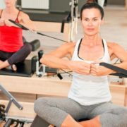 Two woman on reformers during pilates class.