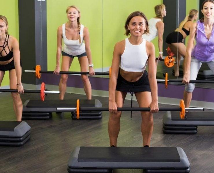 Women in barbell workout class.
