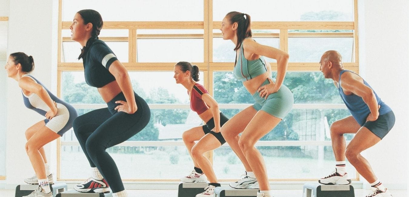 Women in workout class using step benches.