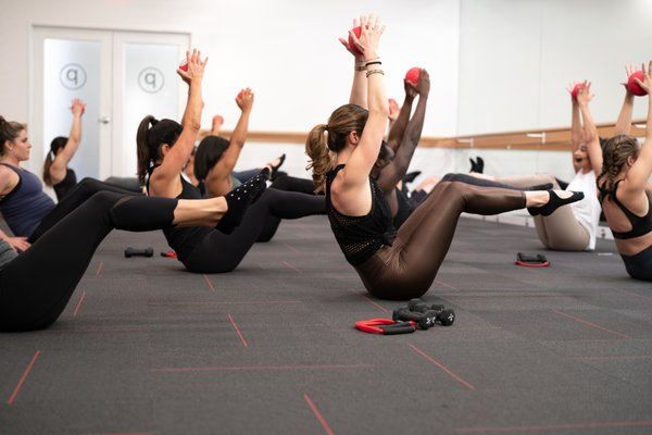 Women raising a ball over their heads during barre workout.