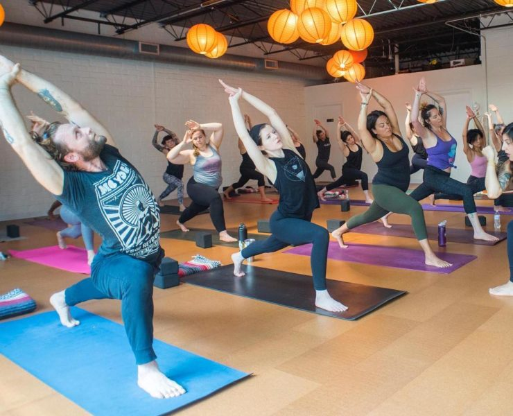 Men and women in a yoga pose during workout class.