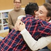 Teenagers hugging in group setting.