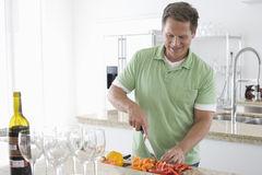 Senior man cutting veggies.