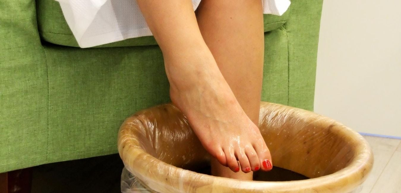 Woman placing her foot in tub.