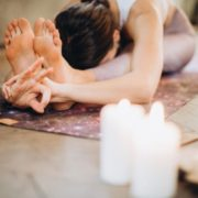 Woman stretching beside candles.