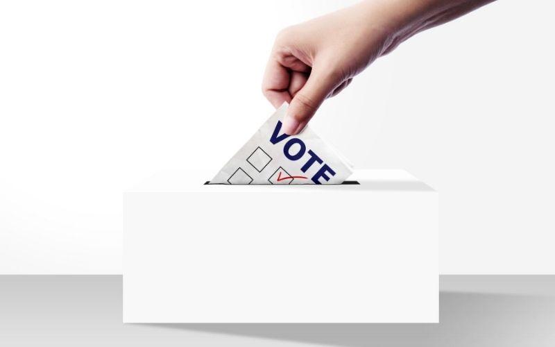 Vote slip going into box.