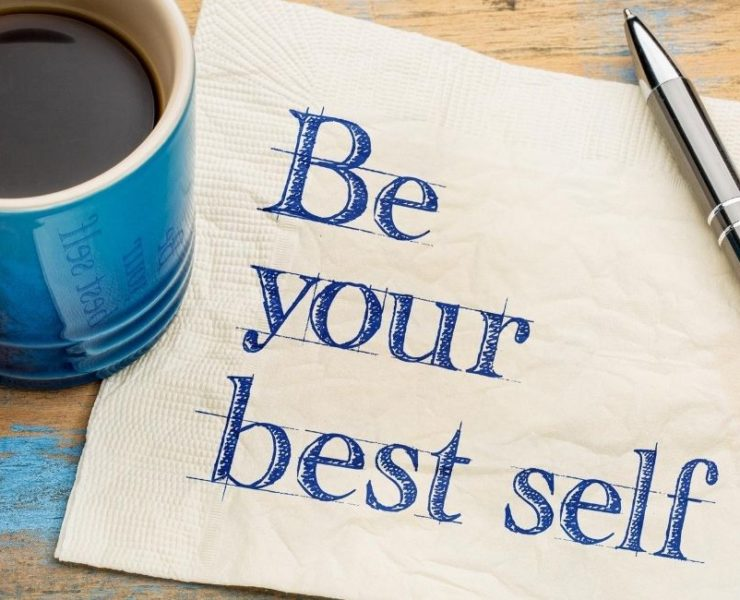 """""""Be your best self"""" on napkin beside a pen and coffee mug."""