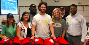 DANSBY SWANSON (MIDDLE) AND REPRESENTATIVES FROM GEORGIA'S OWN CREDIT UNION, THE WILBERT GROUP AND PAPA JOHN'S PREPARE TO SURPRISE GREEN ACRES ELEMENTARY SCHOOL STUDENTS WITH 85 PIZZAS.