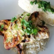 Chicken with rice and veggies on a white plate