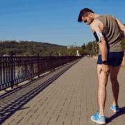 Man running but grabbing at his leg because of sciatica pain