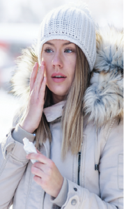 Woman applying lotion in the winter time