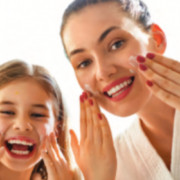 Happy mom and daughter washing faces