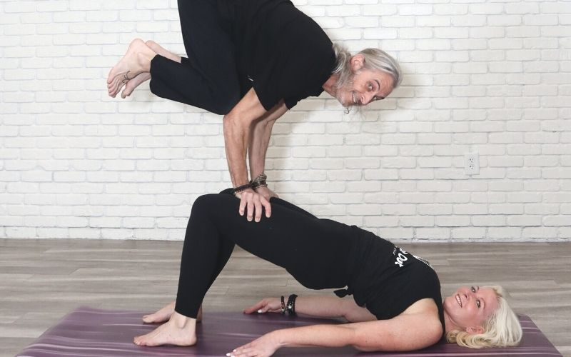 Two Instructors from Peach Out Power Yoga balancing off on another