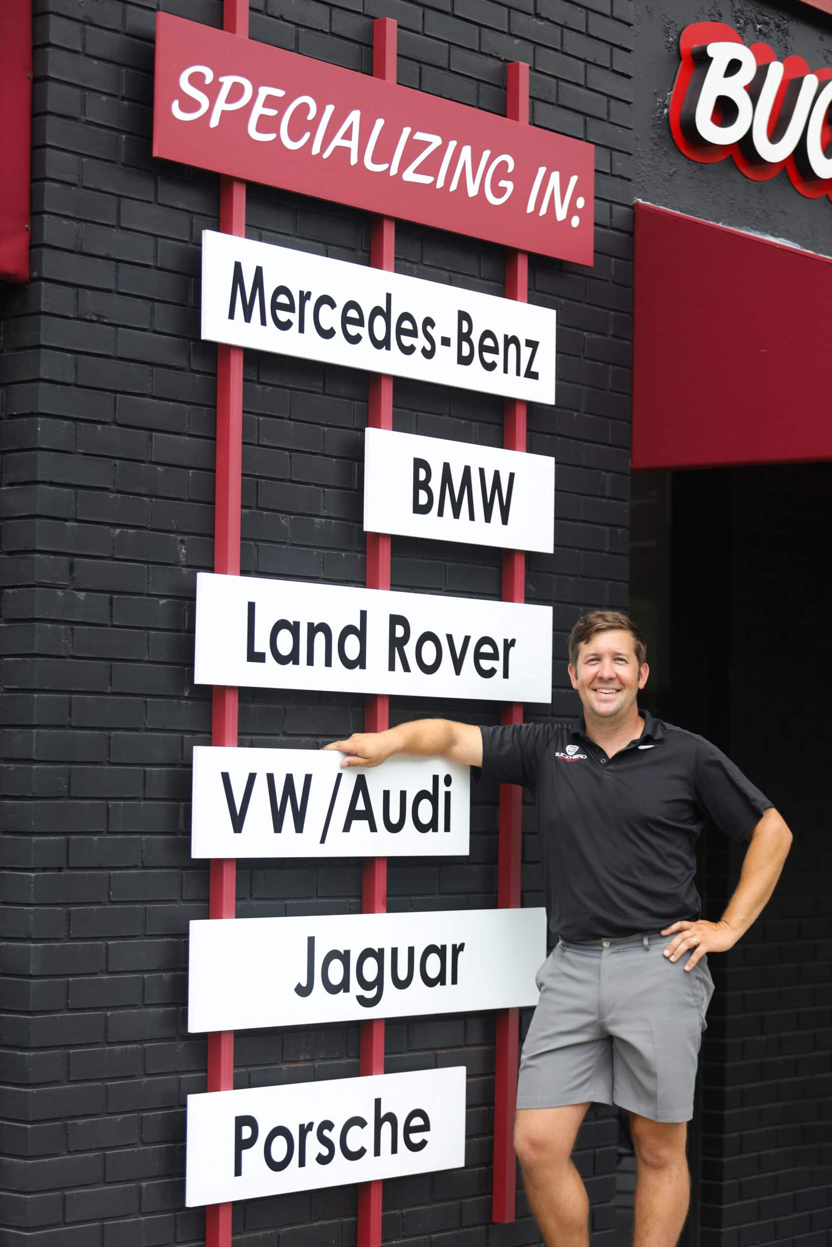 Owner Stephen of Buckhead AutoSport with signs of all the car brands they specialize in