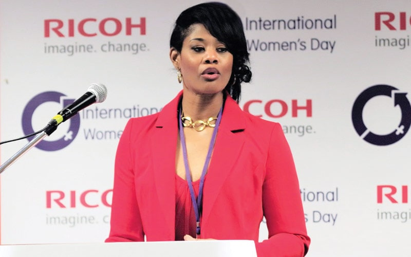 Beautiful African American in red suit speaking at a podium
