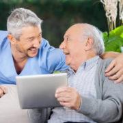Two older men discuss men health myths on a tablet