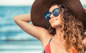Woman wearing a hat to protect herself from the sun on the beach