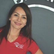 Woman wearing red work shirt smiling in front of her waxing studio.