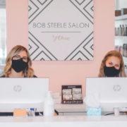 Two women sitting at reception desk wearing masks.