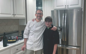 Father and son wearing chef coats posing for photo in their kitchen at home.
