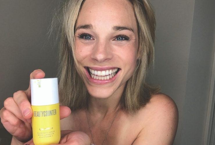 Blonde girl holding yellow skin cleanser bottle.