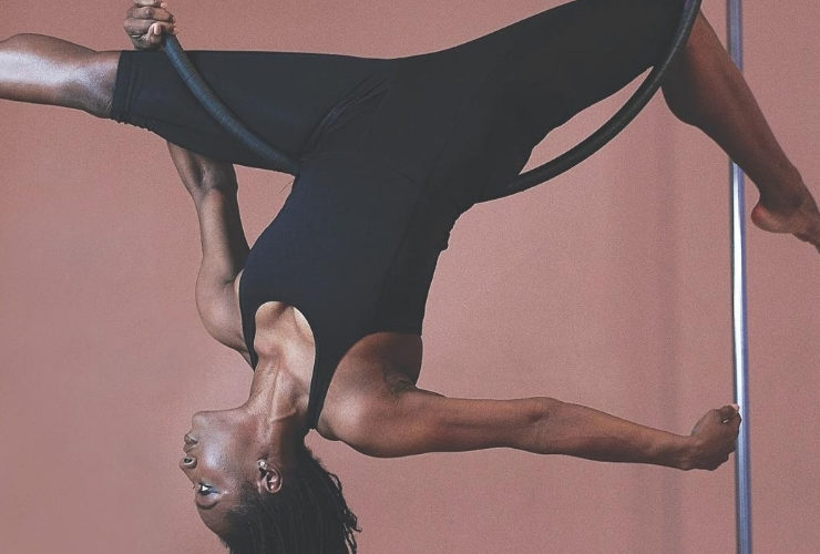 Woman in all black activewear hanging from hoop.