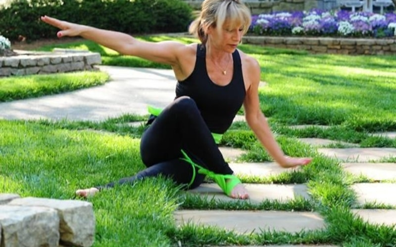 Woman on grass stretching.