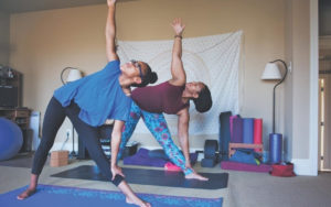 Woman and daughter practicing yoga at home.