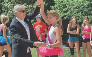"""Teenage girl and her dad dancing outside for a """"prom"""" in their yard."""